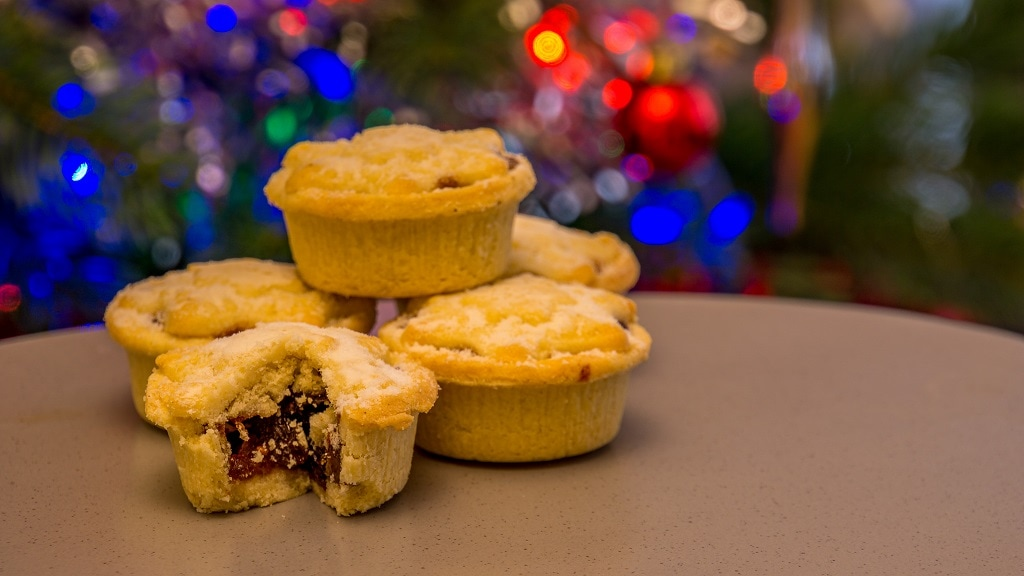 5 small mincemeat pies in front of a christmas themed background