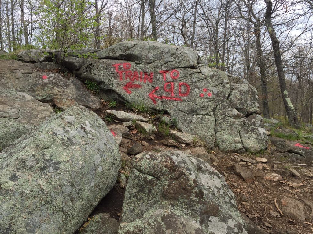 Red writing on the rock to signal the turnoff to go back to the Breakneck Ridge Train Station.
