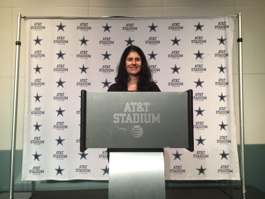 Anisa at the podium in the Cowboys Press Room.
