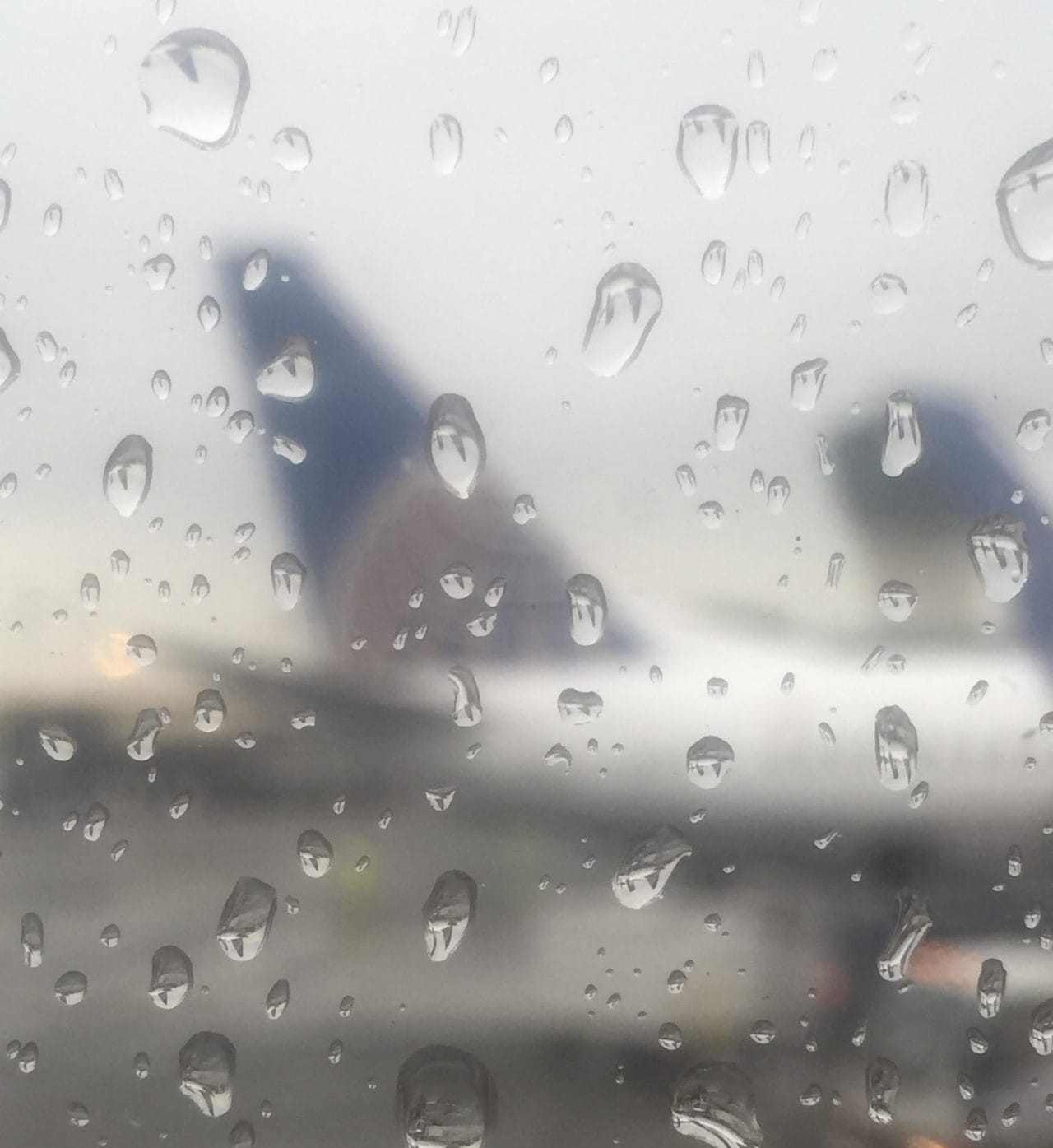 "United planes through a rainy window. Unfortunately you cannot get compensation if the cause is weather. - ""EU Flight Compensation Rules Simplified"" - Two Traveling Texans"