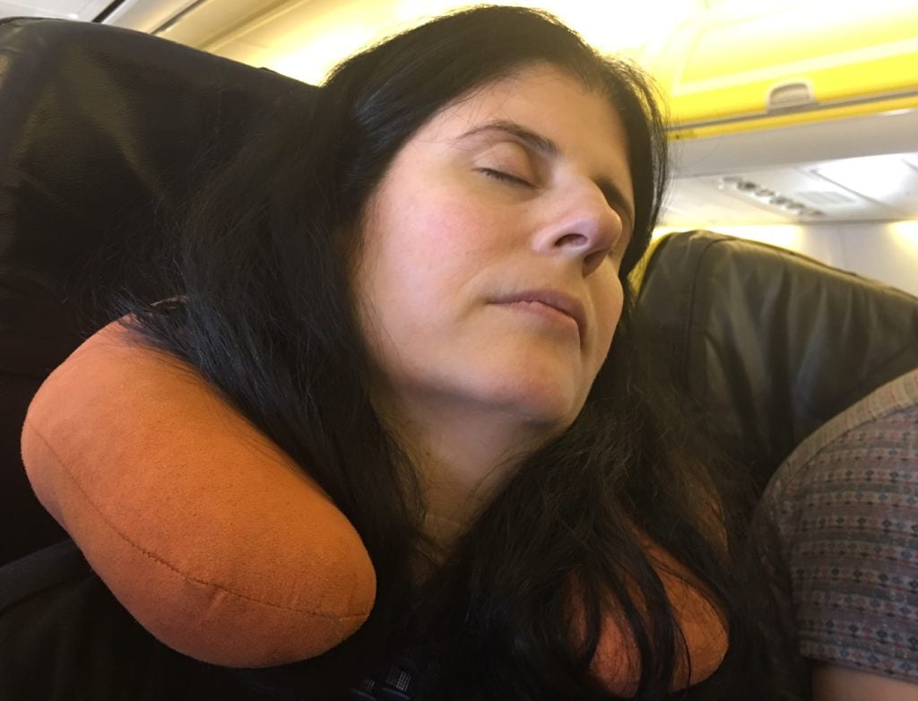 "Anisa using her neck support pillow to help get some sleep on a flight. - ""Neck Support Pillow and Other Travel Sleeping Tips"" - Two Traveling Texans"
