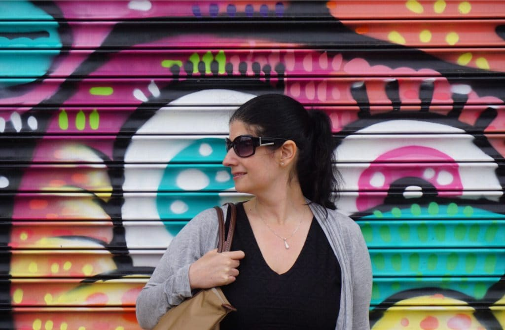 "Anisa posing by one of the colorful murals that is part of the Bushwick Collective. - ""Brooklyn Graffiti and Street Art Tour"" - Two Traveling Texans"