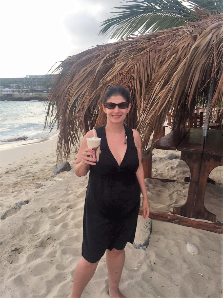 "Anisa enjoying a tropical drink at Guy's Driftwood Boat Bar. - ""Maho Bay: Plane Spotting in St. Maarten"" - Two Traveling Texans"