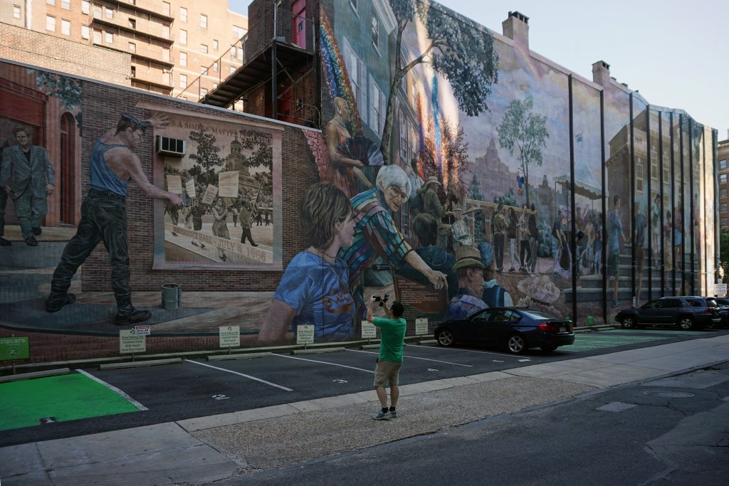 "Pride and Progress by Ann Northup shows the history of the Gay Pride movement. You can see Russell taking a photo and that shows how enormous the mural is! - ""Philadelphia Mural Mile Tour: Get Inspired!"" - Two Traveling Texans"