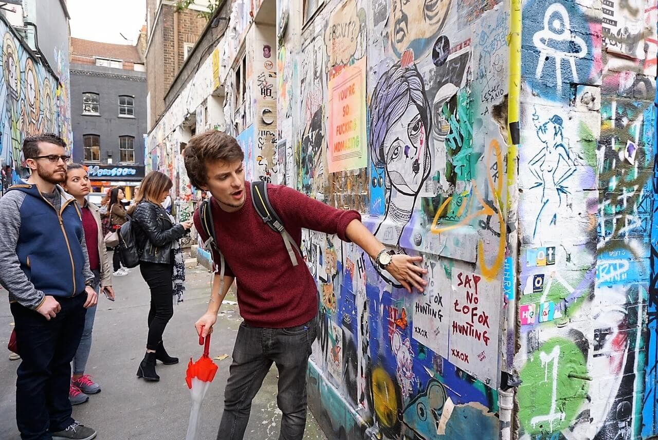 "Nathan shows us some of the smaller pieces of street art in the alley leading to the Star Yard. ""Free Shoreditch Street Art Tour"" - Two Traveling Texans"