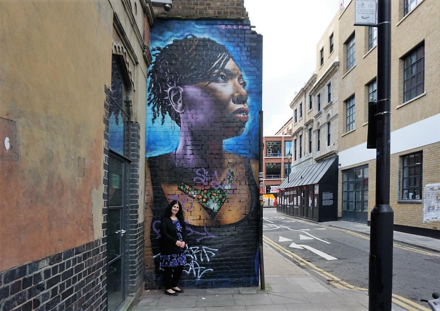"Anisa with one of the portraits from Dreph's ""You are Enough"" campaign. ""Free Shoreditch Street Art Tour"" - Two Traveling Texans"