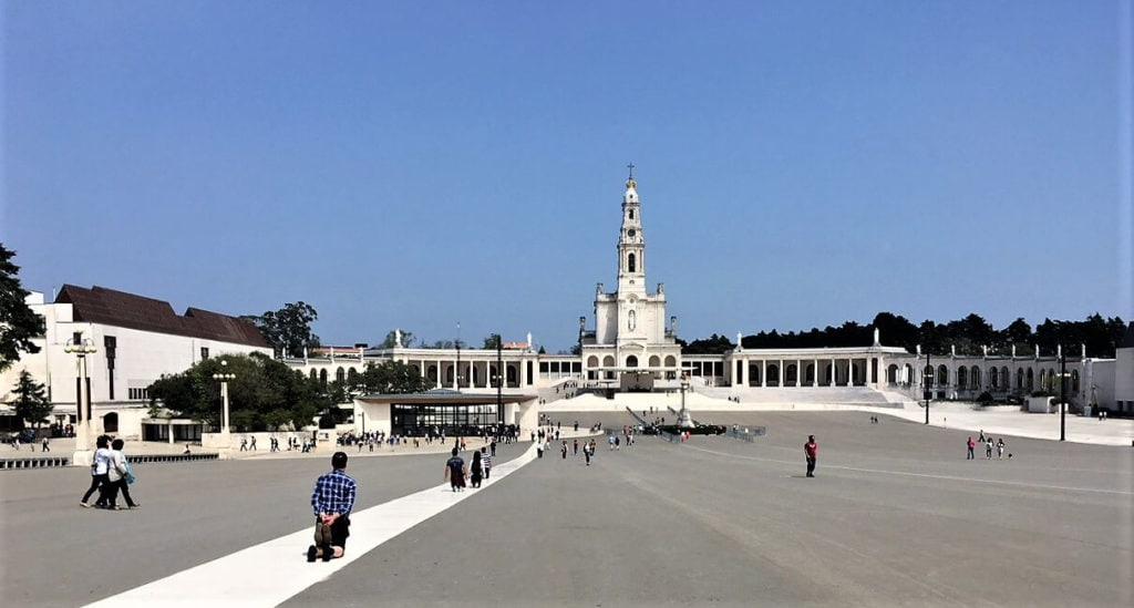 "Pilgrims on their knees in Fatima - ""Our Amazing Portugal Road Trip Itinerary"" - Two Traveling Texans"