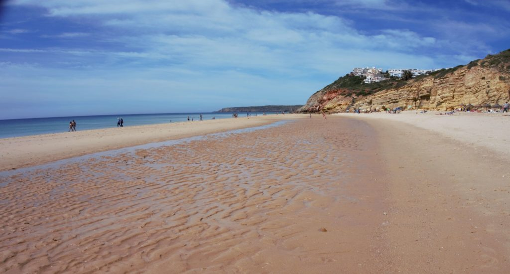 "The beach in Salema in the Algarve.- ""Our Amazing Portugal Road Trip Itinerary"" - Two Traveling Texans"