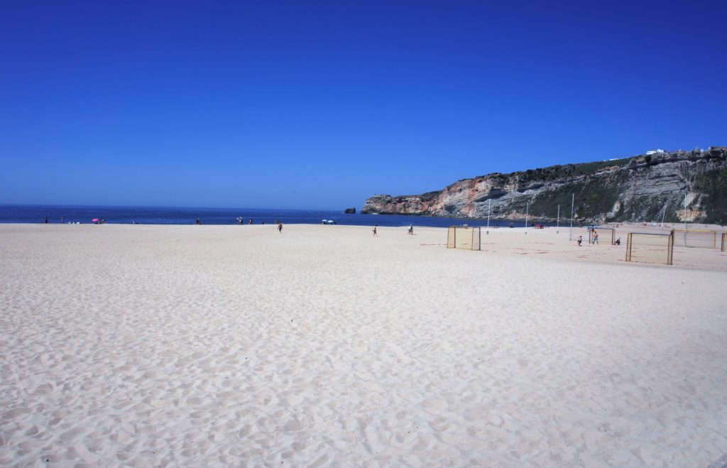 "The sandy beach of Nazare - ""Our Amazing Portugal Road Trip Itinerary"" - Two Traveling Texans"