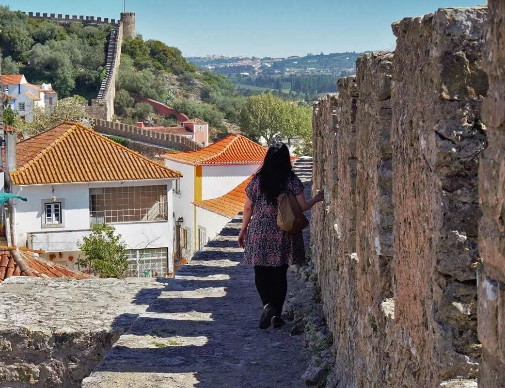 Anisa doing the Obidos city wall walk. - Odibos Portugal - Two Traveling Texans