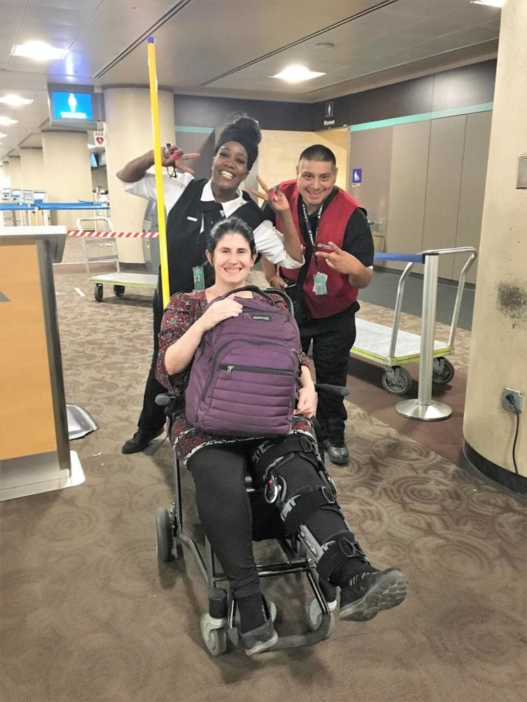 "Anisa in a wheelchair with her leg brace at the Phoenix Airport. - ""Traveling Injured: What Everyone Needs to Know"" - Two Traveling Texans"