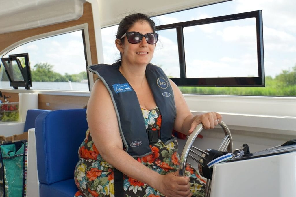 "Anisa driving the Broads boat! - ""Hire a Boat on the Norfolk Broads"" - Two Traveling Texans"