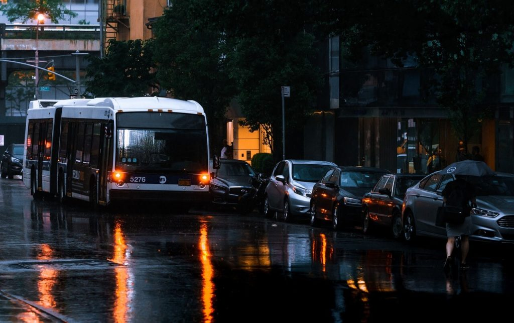NYC bus on rainy street - How to get from LGA to Manhattan - Two Traveling Texans