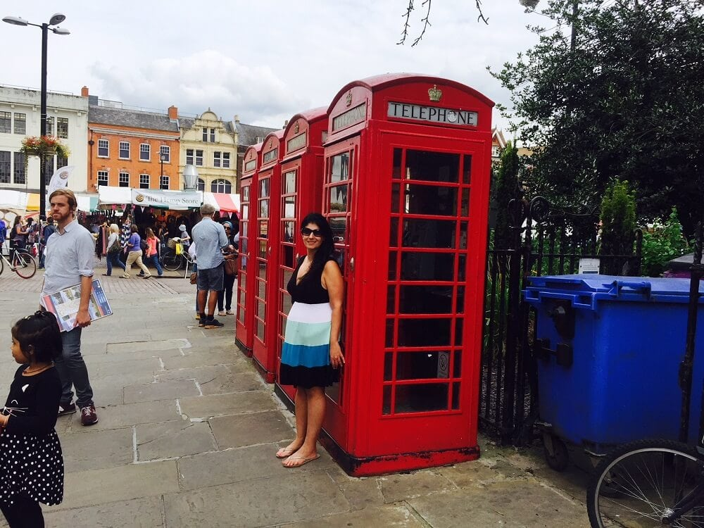 Anisa with phone boxes and the Cambridge Market in the background - visit Cambridge - Two Traveling Texans