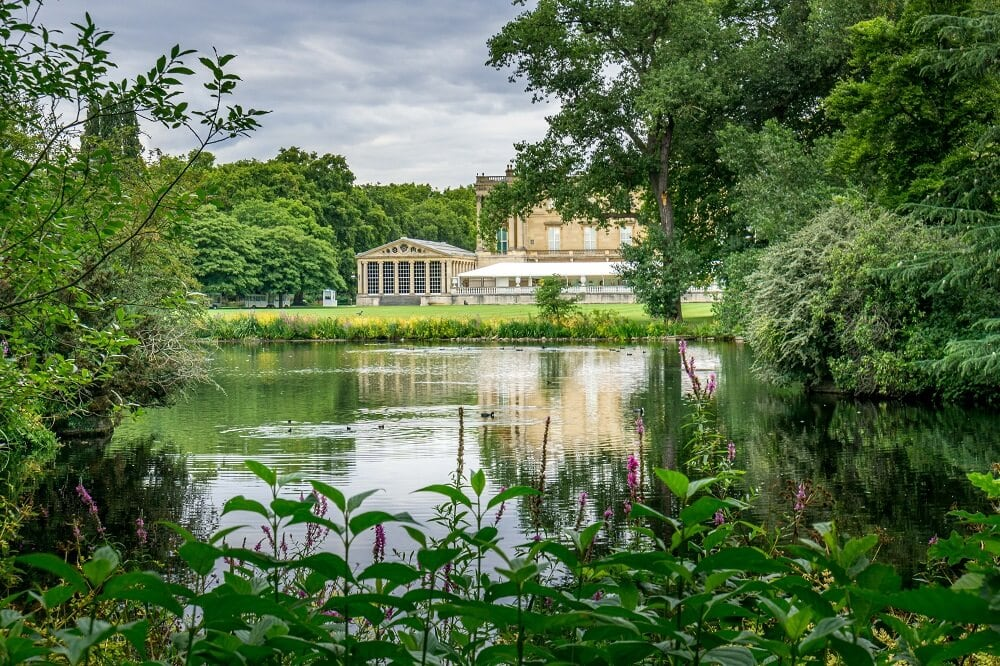 view of the back of Buckingham Palace across the lake in the gardens