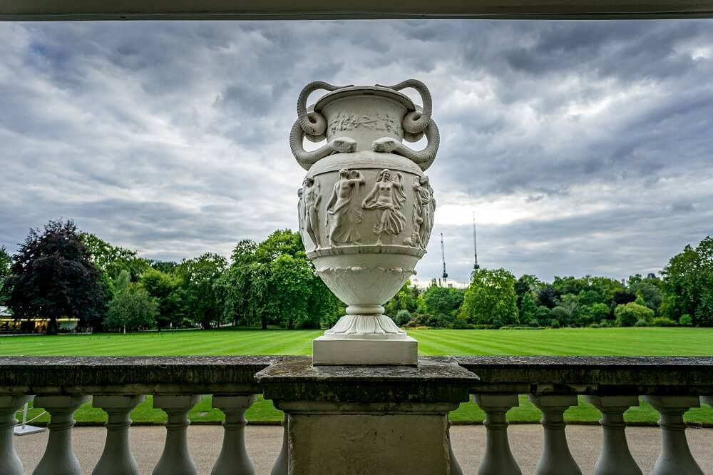 vase in front of the lawn at buckingham palace gardens