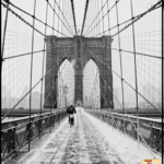 "brooklyn bridge covered in snow with text overlay ""What to do in NYC in the Winter"""