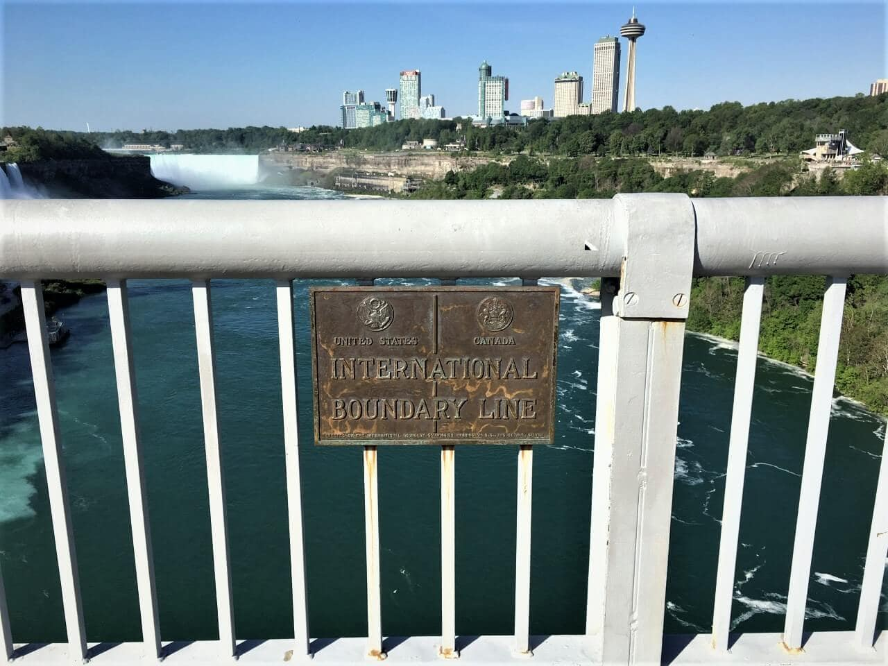 sign pointing out the border between the US and Canada on the Rainbow Bridge in Niagara Falls