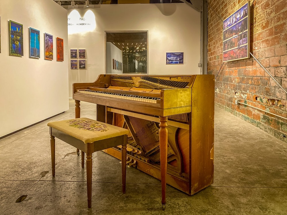 the gallery space at Glasshouse,. There is a piano and artwork on the wall