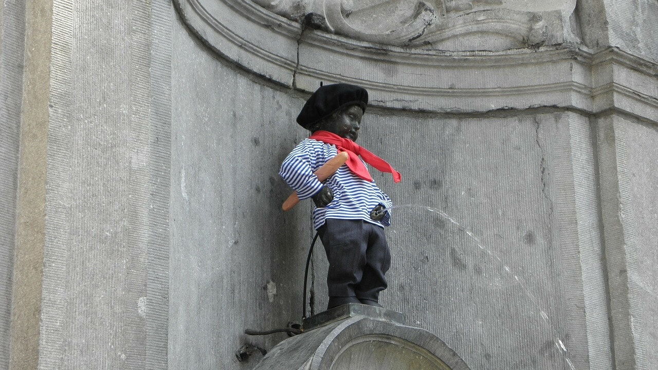 manneken pis dressed up. its a small boy urinating into the fountain
