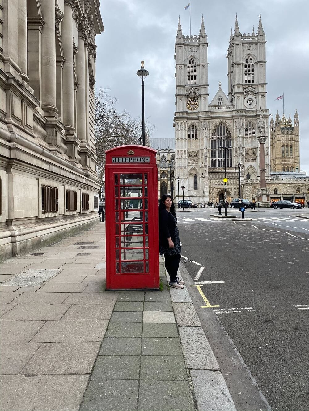 Anisa by red phone box with Westminster Abbey in the background