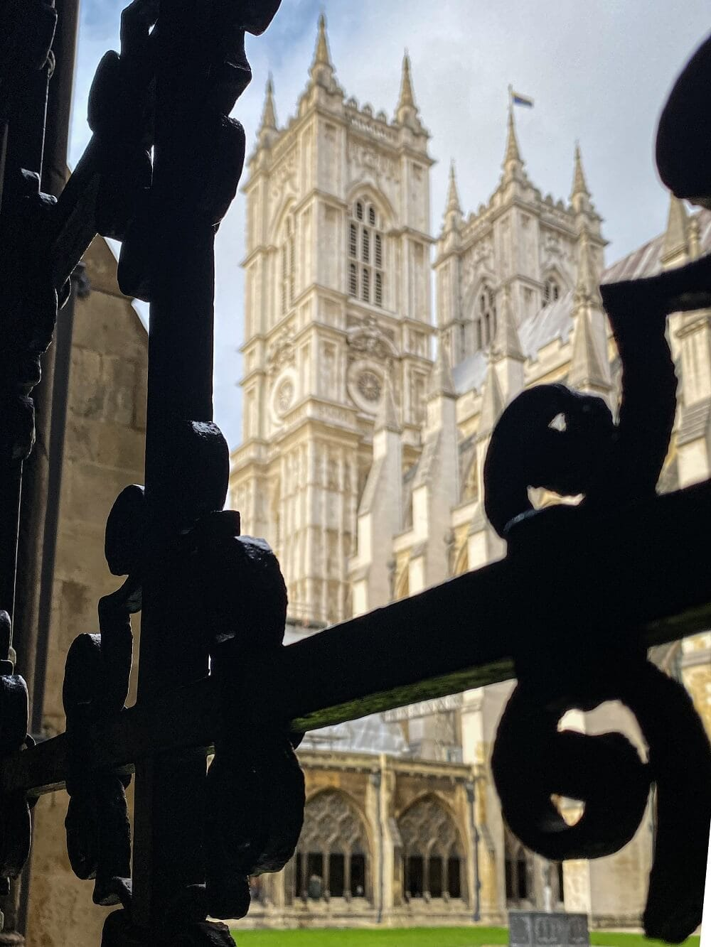 view of Westminster Abbey through iron bars in the Cloisters