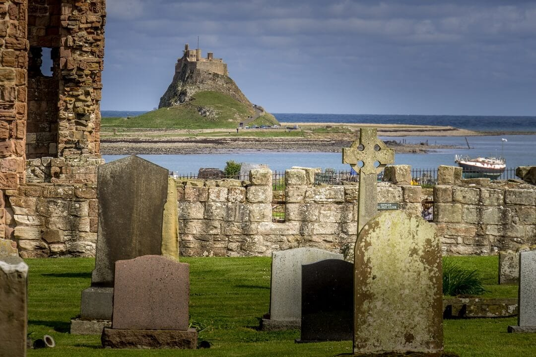 view of Lindisfarne castle with cemetery in the foreground