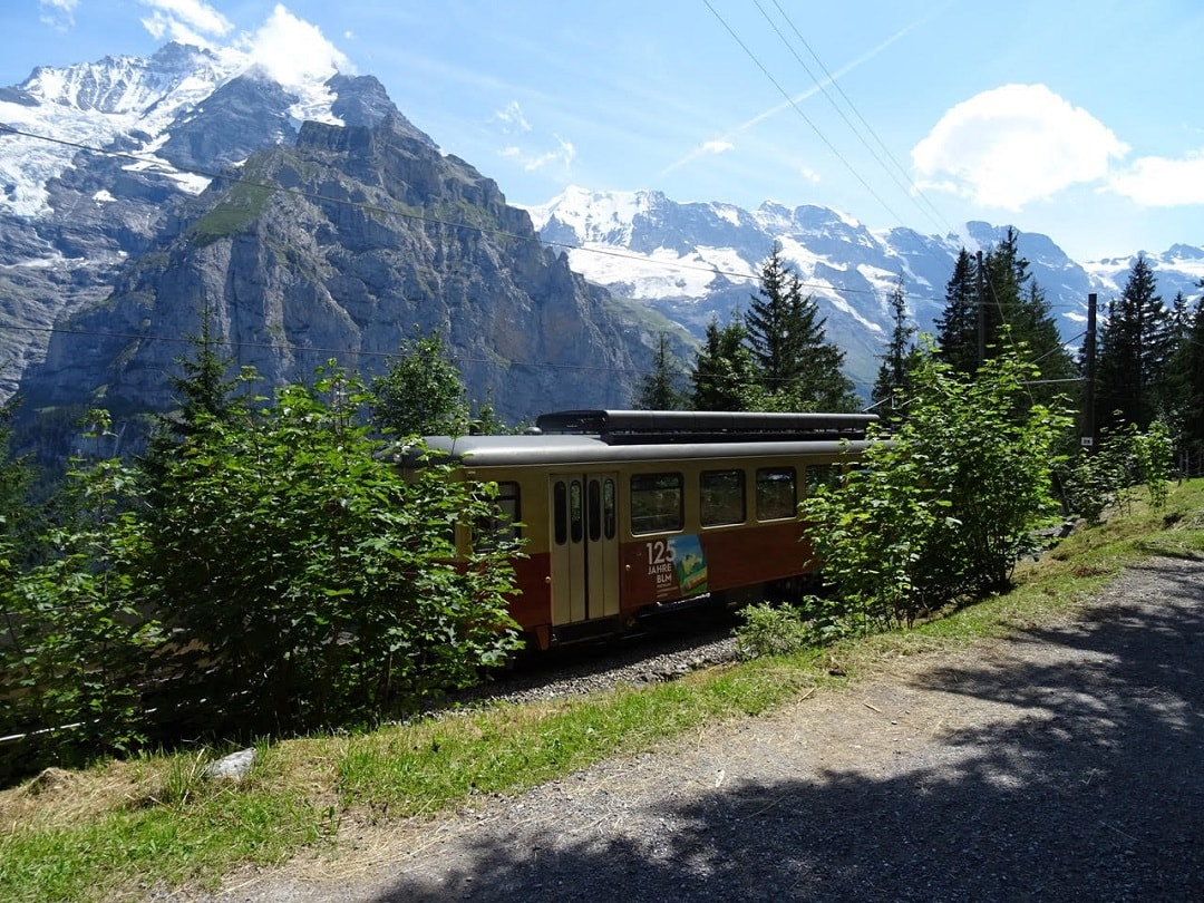 the train passing along the track towards Murren. The walking path runs alongside the train track.