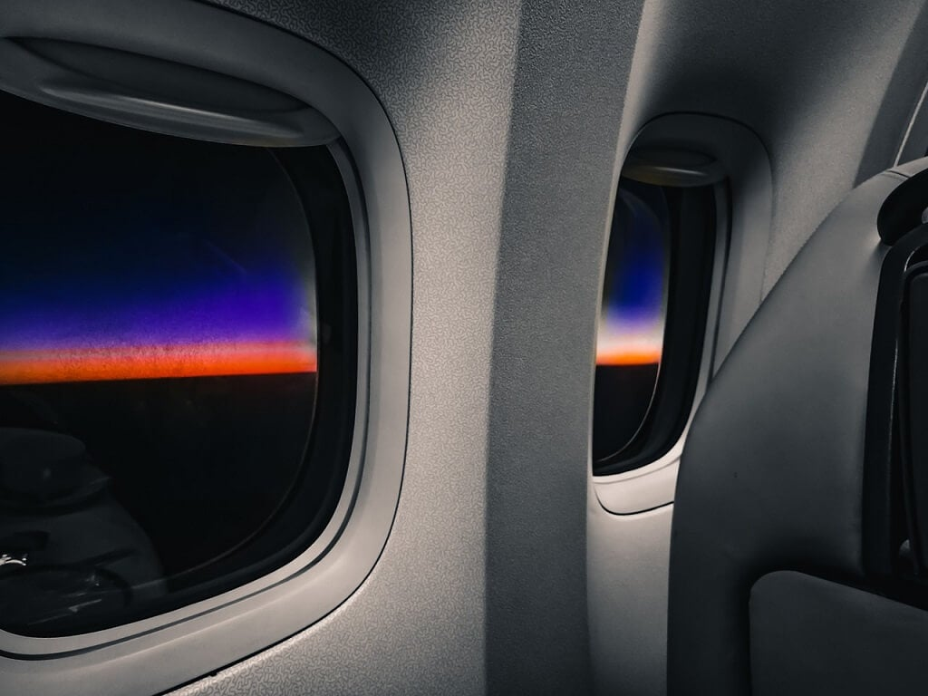 sunrise through the window of an airplane on a red eye flight