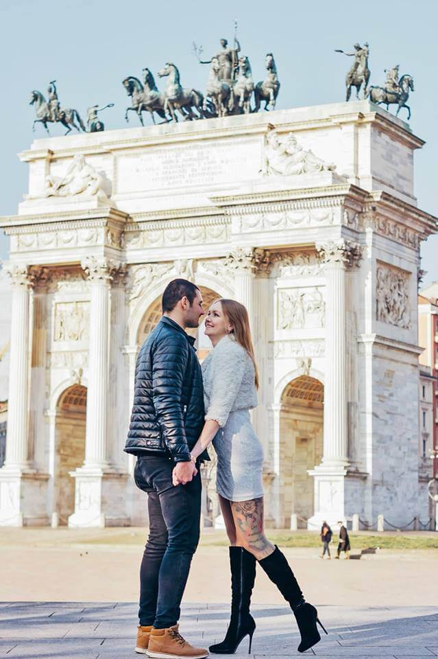 couple holding hands by the Arch of Peace in Milan Italy