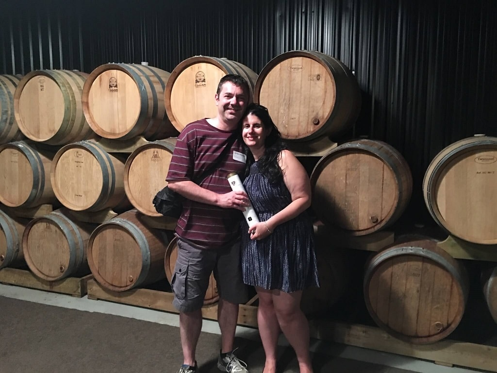 Anisa and Russell holding some ice wine in front of wine barrells in Niagara on the Lake