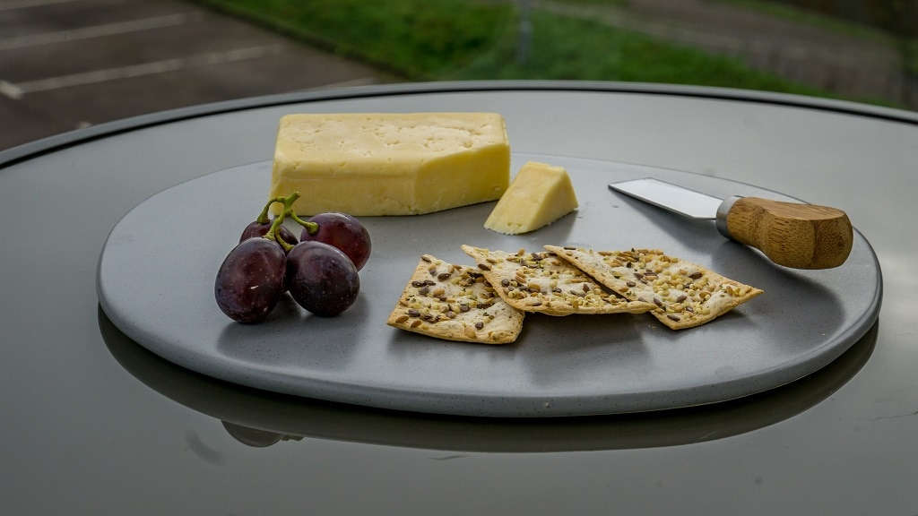 british cheddar cheese with grapes, crackers, and a cheese knife