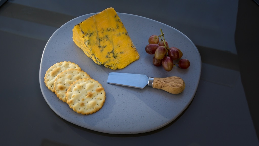 shropshire blue cheese with crackers grapes and a cheese knife