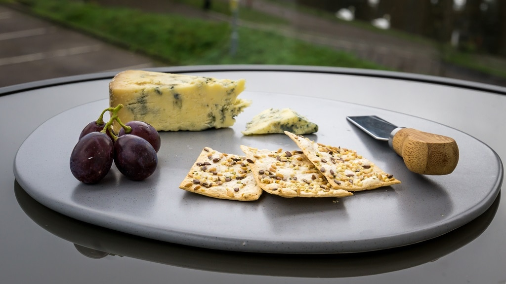 Stilton cheese with grapes, crackers, and a cheese knife