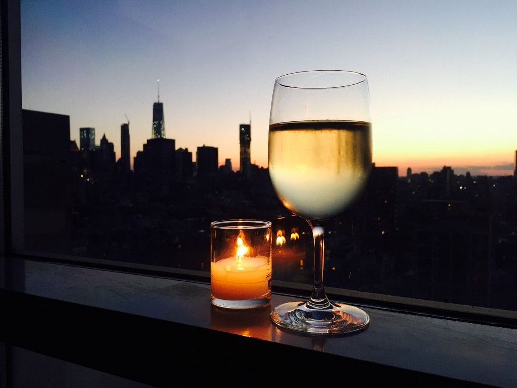 wine glass with sunset and nyc skyline in the background