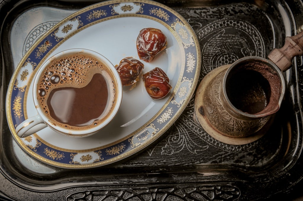 cup of turkish coffee with dates on a serving tray