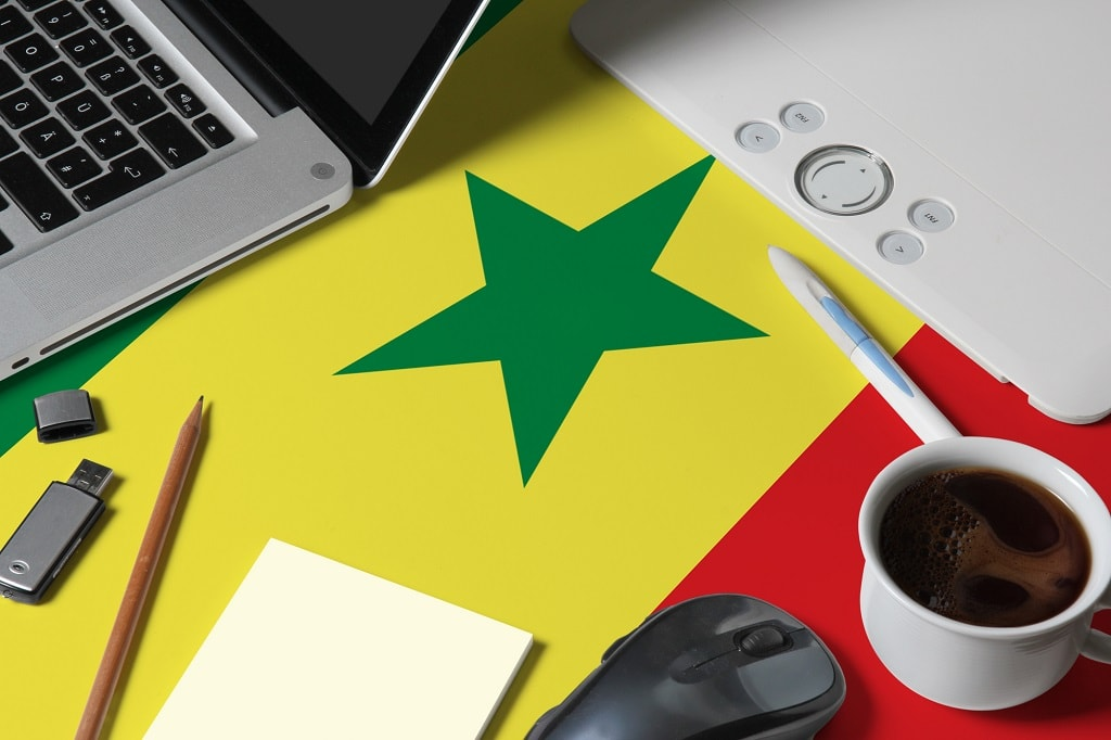 Senegal national flag on top view work space of creative designer with laptop, computer keyboard, usb drive, graphic tablet, coffee cup, mouse on wooden table.