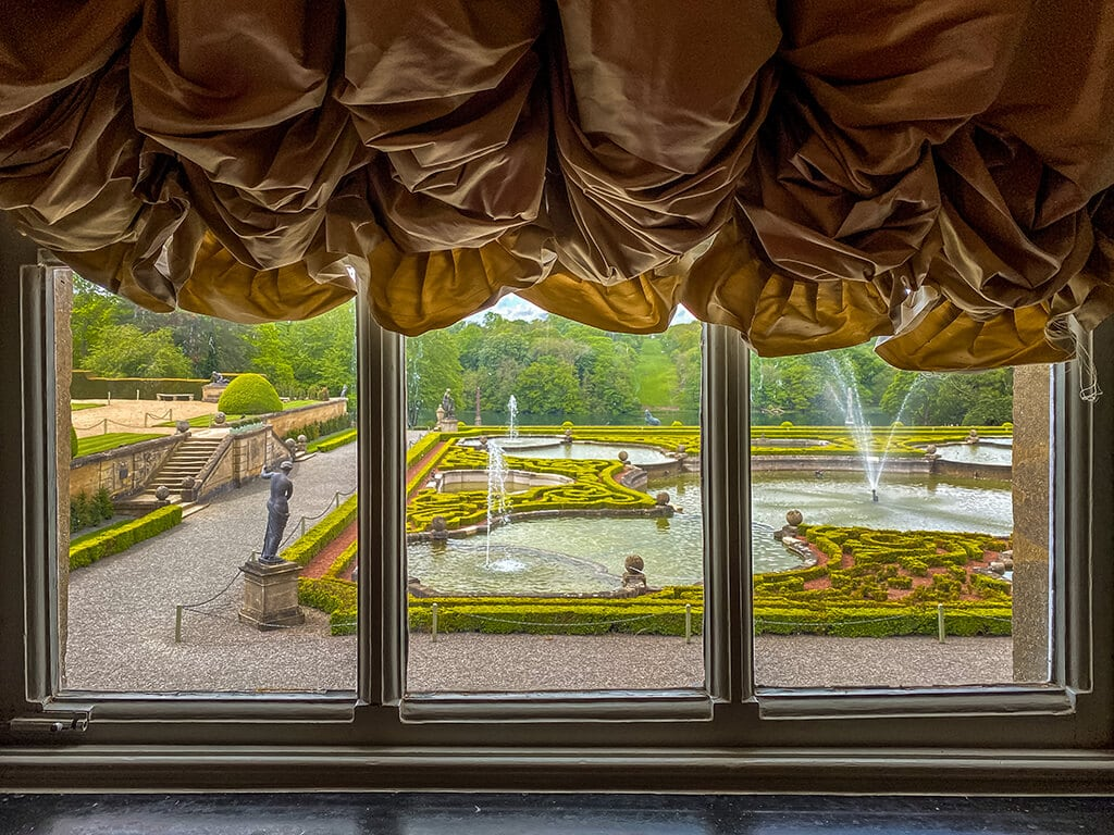 view of the formal gardens from the library of blenheim palace